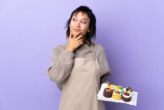 Jovem uruguaia segurando muitos mini bolos diferentes sobre parede roxa isolada, pensando uma idéia