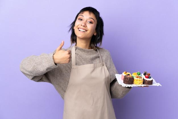 Jovem uruguaia segurando muitos mini bolos diferentes sobre roxo isolado dando um polegar para cima gesto