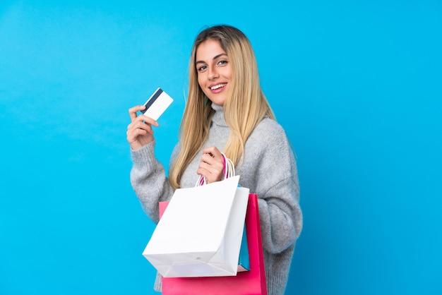 Jovem uruguaia segurando sacolas de compras e cartão de crédito