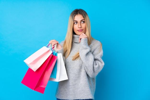 Jovem uruguaia segurando sacolas de compras e pensando