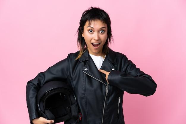 Jovem uruguaia segurando um capacete de moto sobre parede rosa isolada com expressão facial de surpresa