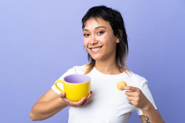 Jovem uruguaia sobre fundo roxo isolado, segurando macarons franceses coloridos e um copo de leite