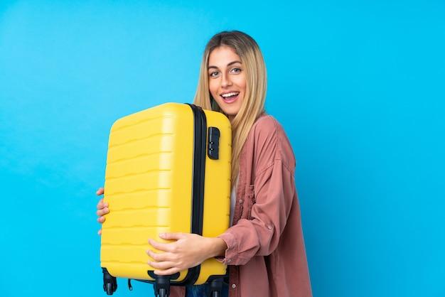 Jovem uruguaia sobre parede azul isolada em férias com mala de viagem e surpresa