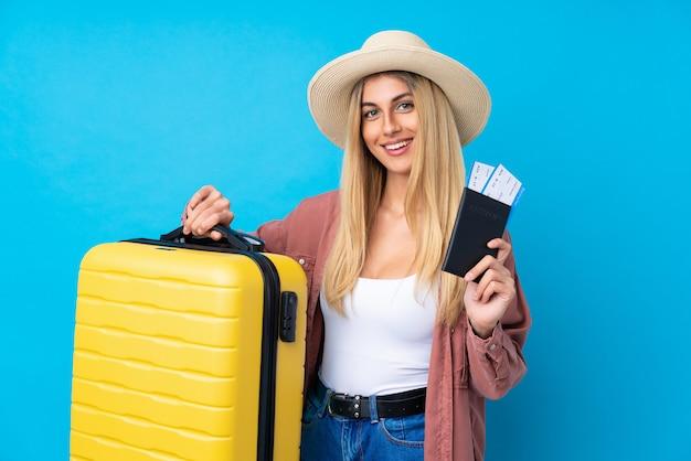 Jovem uruguaia sobre parede azul isolada em férias com mala e passaporte