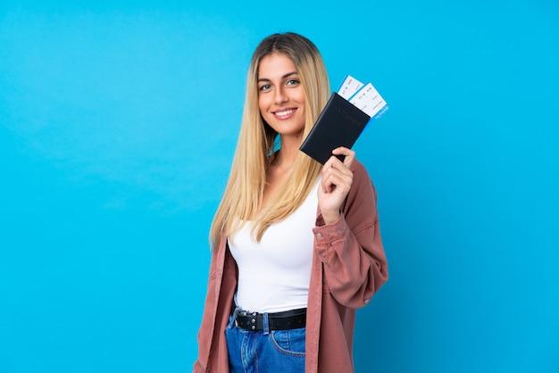 Jovem uruguaia sobre parede azul isolada feliz em férias com bilhetes de avião e passaporte