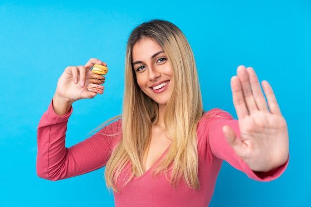 Jovem uruguaia sobre parede azul isolada segurando macarons franceses coloridos e saudação