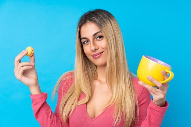 Jovem uruguaia sobre parede azul isolada segurando macarons franceses coloridos e um copo de leite