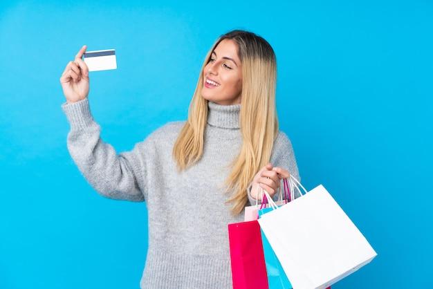 Jovem uruguaia sobre parede azul isolada, segurando sacolas de compras e cartão de crédito