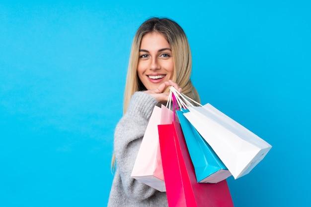 Jovem uruguaia sobre parede azul isolada segurando sacolas de compras e sorrindo
