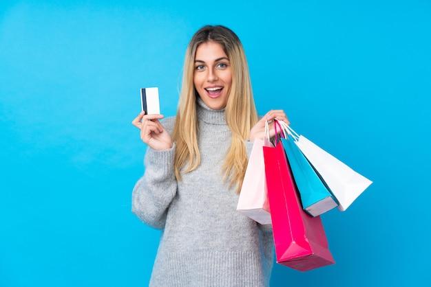 Jovem uruguaia sobre parede azul isolada segurando sacolas de compras e surpreendeu