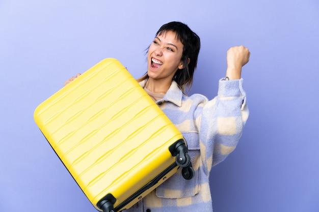 Jovem uruguaia sobre parede roxa em férias com mala de viagem