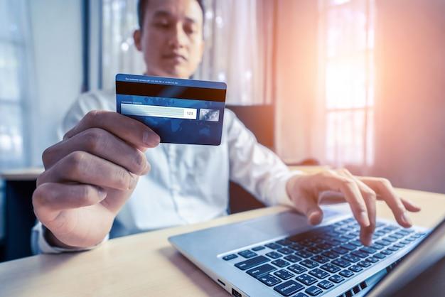 Jovem usa cartão de crédito para fazer compras de pagamento on-line em um aplicativo ou site de computador laptop