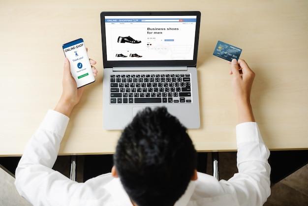 Jovem usa cartão de crédito para fazer compras de pagamento on-line no aplicativo ou site do computador laptop