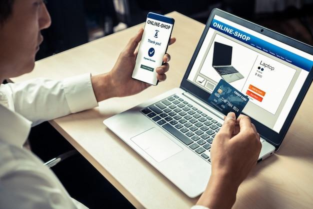 Jovem usa cartão de crédito para fazer compras de pagamento on-line no aplicativo ou site do computador portátil.