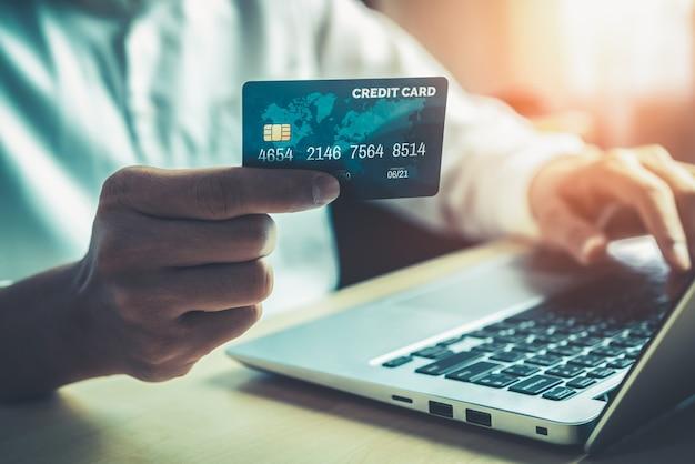 Jovem usa cartão de crédito para fazer compras online