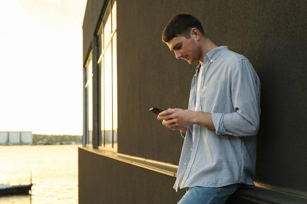 Jovem usa um telefone ao ar livre.