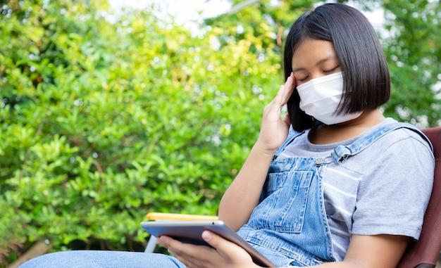 Jovem usa uma máscara de proteção e dor de cabeça depois de trabalhar duro pelo tablet para estudar on-line no jardim em casa. impedir o contato do coronavírus. educação em casa.