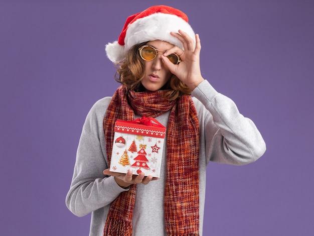 Jovem usando chapéu de papai noel de natal e óculos amarelos com um lenço quente em volta do pescoço segurando um presente de natal fazendo uma placa de ok olhando através desta placa em cima da parede roxa