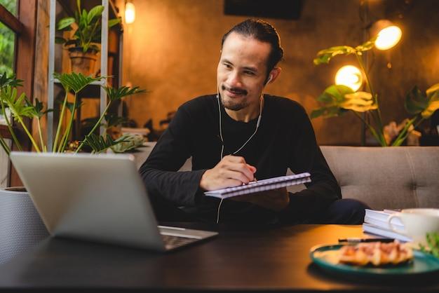 Jovem usando computador laptop ou tablet para trabalhar e aprender a comunicação on-line em casa, tecnologia de educação ciberespaço para empresários ou estudantes usando para trabalhar, empresário moderno