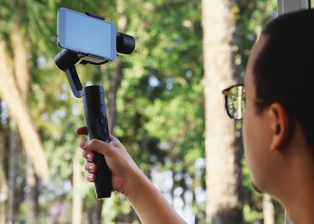 Jovem usando estabilizador para celular e filmando a floresta