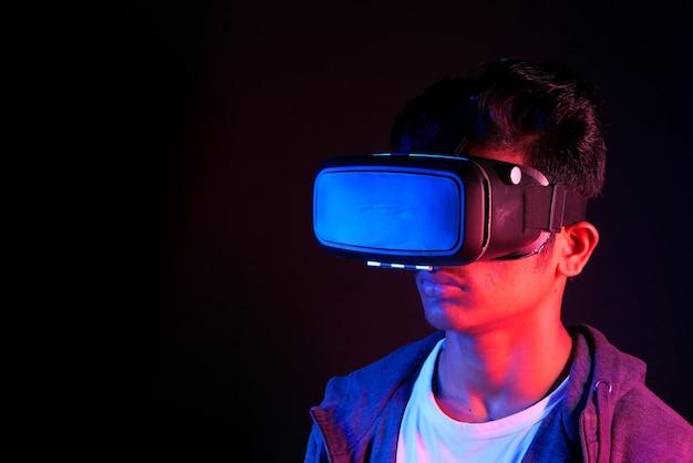 Jovem usando fone de ouvido de realidade virtual, caixa de vr à noite
