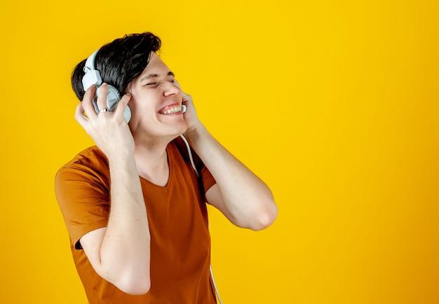 Jovem usando fones de ouvido e apreciar a música; em um fundo de ouro amarelo, as emoções de um jovem