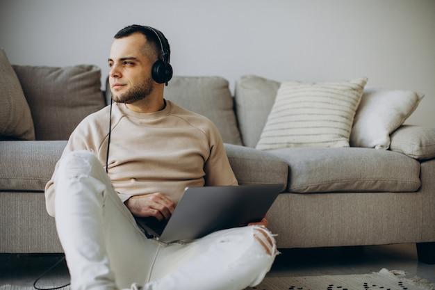 Jovem usando fones de ouvido e usando o computador em casa