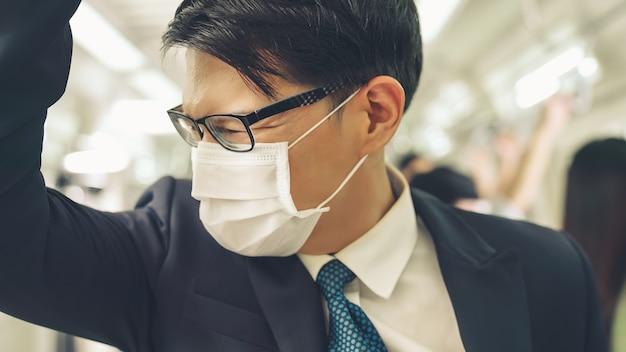 Jovem usando máscara facial viaja em um trem lotado de metrô