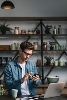 Jovem usando o celular com o laptop; tablet digital e caneca de café no balcão da cozinha