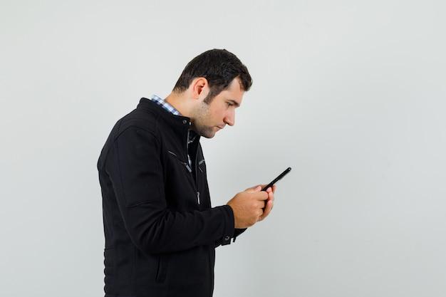 Jovem usando o celular em uma camisa, jaqueta e parecendo ocupado.