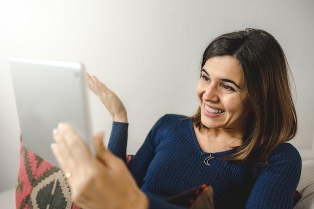 Jovem usando o tablet para uma vídeo chamada para um amigo ou família, feliz e sorridente durante a conversa.