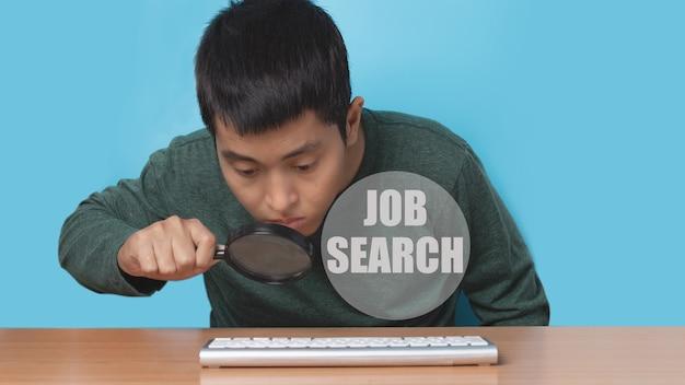 Jovem usando o teclado do computador online com lupa para procurar emprego. conceito de procura de emprego.