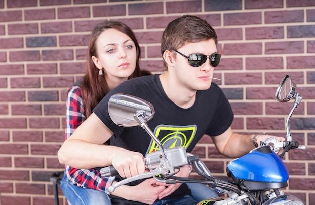 Jovem usando óculos escuros e mastigando palito de dente, andando de motocicleta em frente à parede de tijolos com uma jovem passageira nas costas