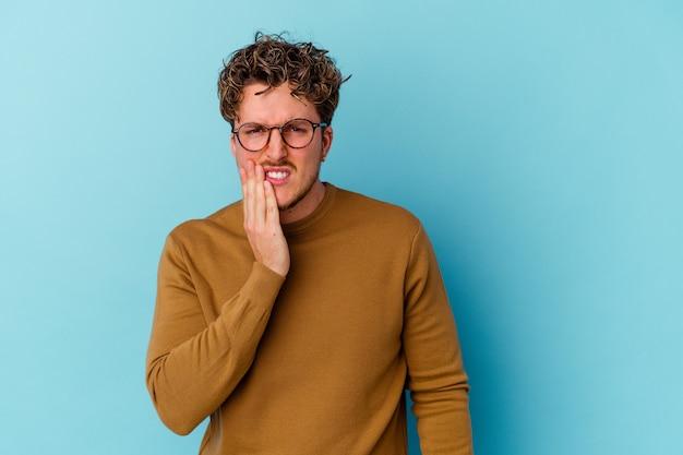 Jovem usando óculos isolados na parede azul, com forte dor nos dentes, dor nos molares