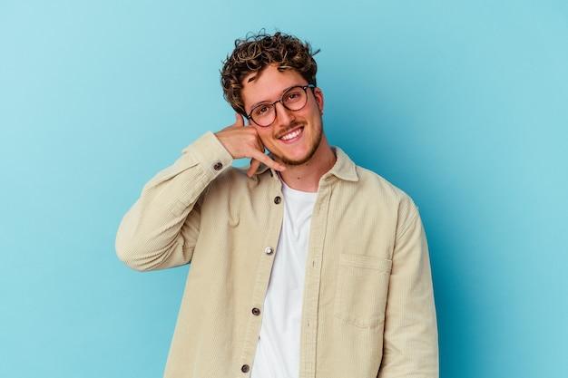 Jovem usando óculos isolados na parede azul, mostrando um gesto de chamada de celular com os dedos
