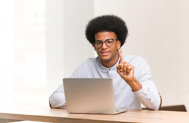 Jovem usando seu laptop, mostrando o número um