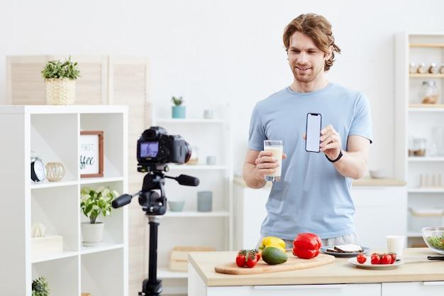Jovem usando seu telefone celular e preparando um coquetel saudável de vegetais e filmando o blog para a câmera