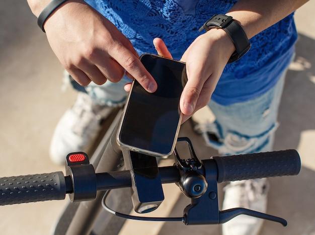 Jovem usando smartphone para desbloquear uma scooter elétrica compartilhada. fechar-se