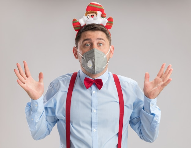 Jovem usando suspensórios gravata borboleta na borda com papai noel usando máscara facial protetora, olhando para a câmera, confuso e surpreso, com os braços levantados em pé sobre um fundo branco