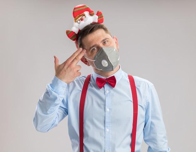 Jovem usando suspensórios gravata-borboleta na borda com papai noel usando máscara facial protetora olhando para a câmera fazendo gesto de pistola com os dedos sobre o templo em pé sobre fundo branco