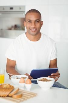 Jovem usando tablet e tomando café da manhã na cozinha em casa