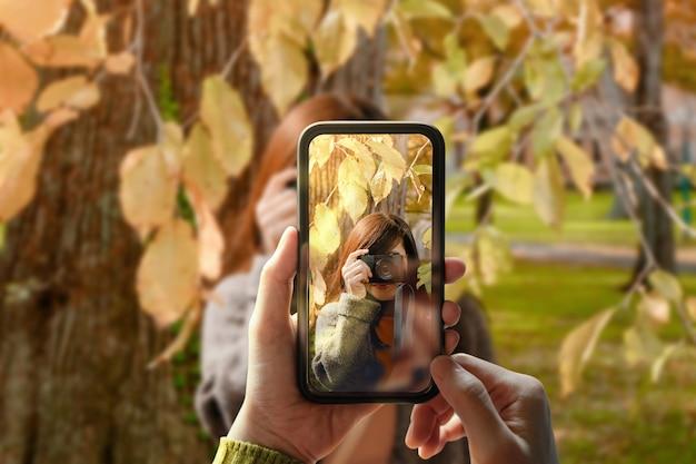 Jovem usando telefone celular para tirar uma foto para um amigo no parque ao ar livre. o modelo na tela com câmera digital faz o mesmo. vista frontal