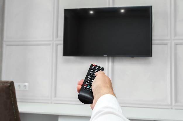 Jovem, usando, tv, controle remoto