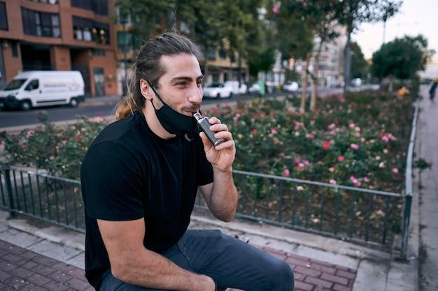 Jovem usando um cigarro eletrônico na rua