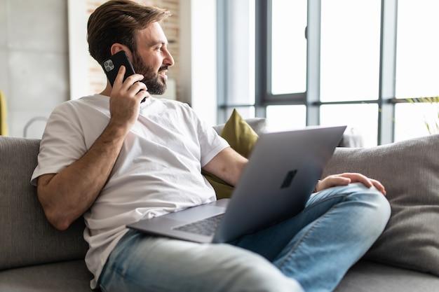Jovem, usando um laptop enquanto fala ao telefone, sentado no sofá em casa