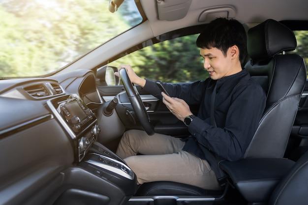 Jovem usando um smartphone enquanto dirige um carro
