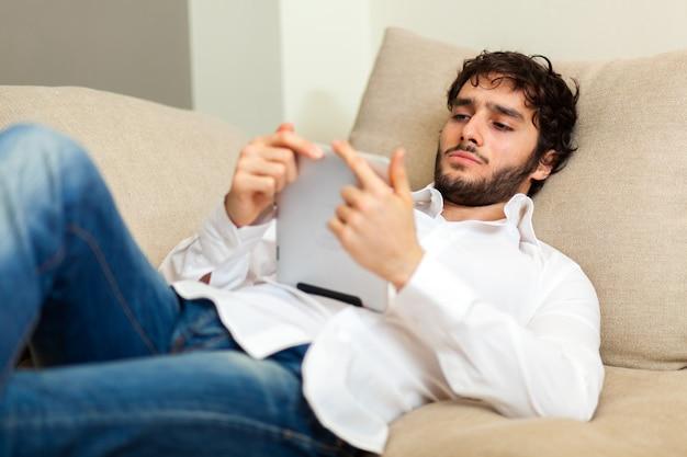 Jovem usando um tablet digital deitado no sofá