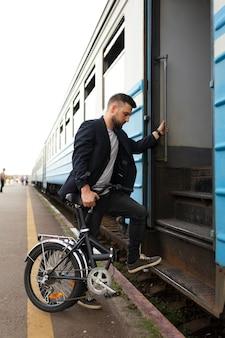 Jovem usando uma bicicleta dobrável enquanto viaja de trem