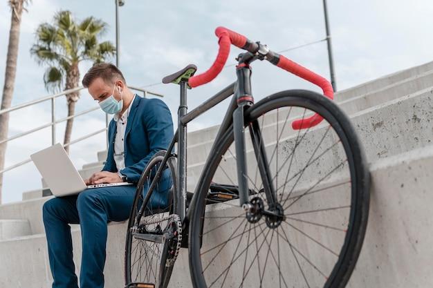 Jovem usando uma máscara médica enquanto está sentado ao lado de sua bicicleta