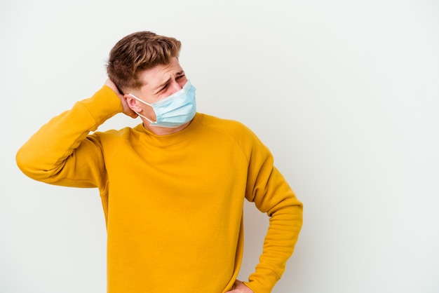 Jovem usando uma máscara para coronavírus isolada na parede branca tocando a parte de trás da cabeça, pensando e fazendo uma escolha